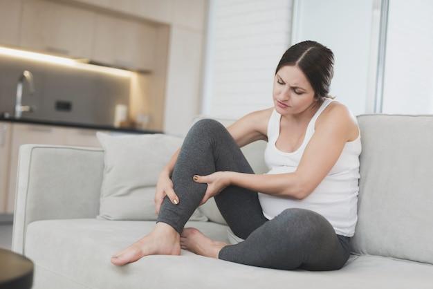 Una mujer embarazada se sienta en casa en un sofá ligero. le duelen las piernas.
