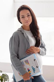 Mujer embarazada sonriente en casa con portapapeles