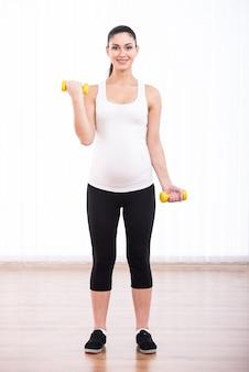 La mujer embarazada sonriente hermosa está haciendo deporte