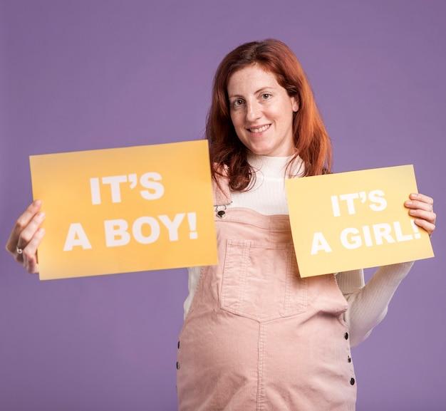 Mujer embarazada sonriente que sostiene el papel con género del bebé