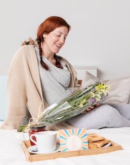 Mujer embarazada sonriente sorprendida en casa