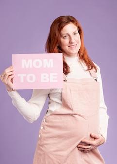 Mujer embarazada sonriente sosteniendo papel con mamá para ser mensaje