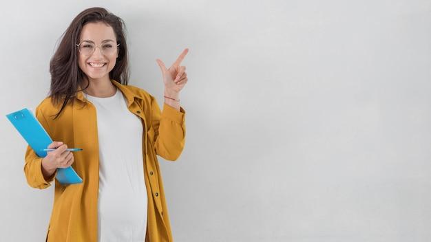Mujer embarazada sonriente sosteniendo el portapapeles y apuntando hacia arriba con espacio de copia