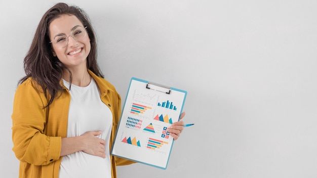 Mujer embarazada sonriente sosteniendo el portapapeles y su vientre