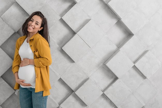 Mujer embarazada sonriente sosteniendo su vientre con espacio de copia