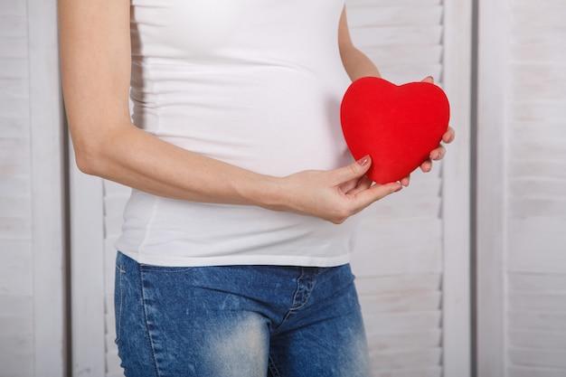 Mujer embarazada sosteniendo un corazón rojo juguete close up. juguete en forma de corazón en la pared de la panza embarazada. esperando bebé 9 meses de embarazo saludable. manos humanas sostienen juguete rojo en forma de corazón