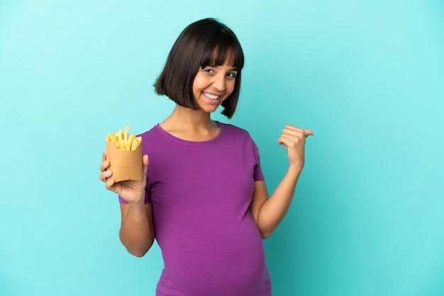 Mujer embarazada sosteniendo patatas fritas sobre fondo aislado apuntando hacia el lado para presentar un producto