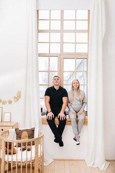 Una mujer embarazada y su esposo esperan al bebé y están sentados en una gran ventana panorámica