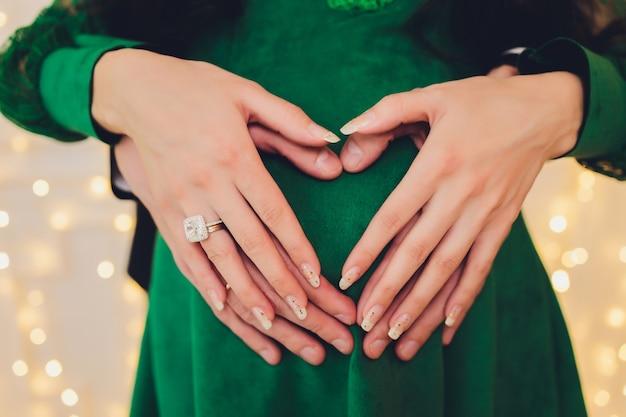 Mujer embarazada y su esposo sosteniendo sus manos en forma de corazón en su panza.