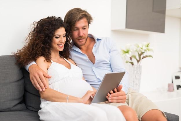 Mujer embarazada y su marido usando una tableta en casa