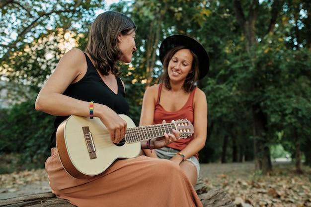 Mujer embarazada con su pareja tocando el ukelele en un parque mientras disfrutan de la compañía de los demás