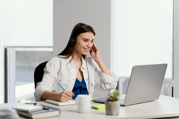 Mujer embarazada, tener una llamada, en el trabajo