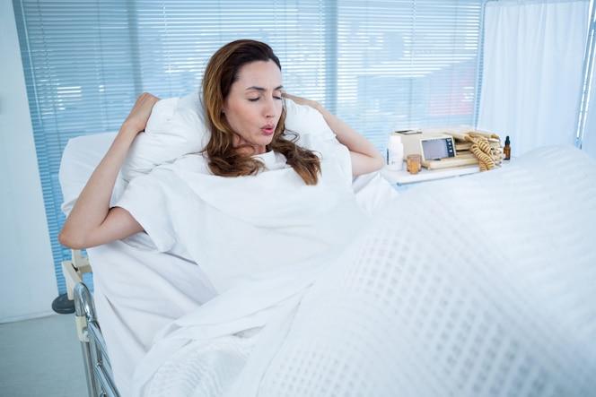 Mujer embarazada teniendo dolores de parto en la habitación del hospital