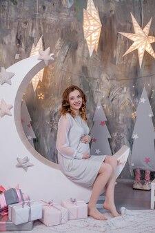 Mujer embarazada tocando su vientre en estudio de decoración con estrellas luna maternidad
