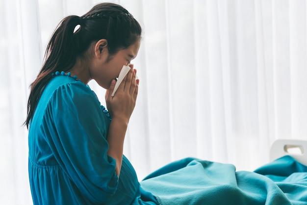 Mujer embarazada usando una toalla de papel para limpiar los mocos debido a la gripe.