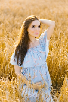 Una mujer embarazada con un vestido azul sostiene su mano sobre su estómago en un campo de trigo al atardecer