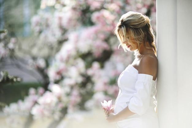 Mujer embarazada en un vestido blanco de pie cerca de la pared