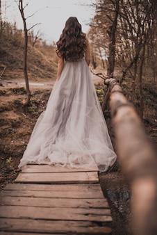 Una mujer embarazada con un vestido largo ligero.