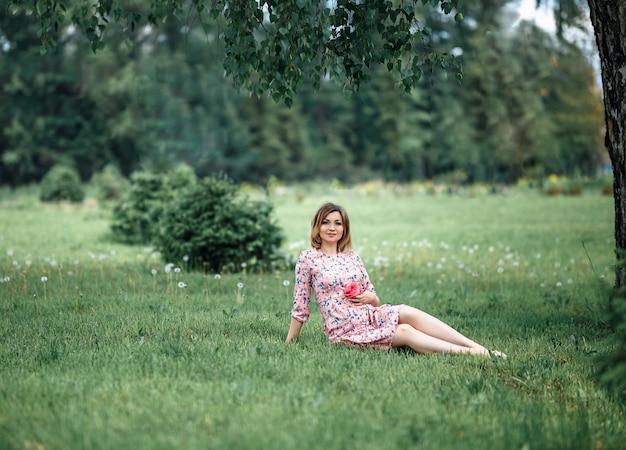 Mujer embarazada en vestido rosa sentada sobre hierba y tocando topetón