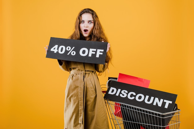 Mujer emocionada en abrigo con descuento 40% signo y coloridas bolsas de compras en carro aislado sobre amarillo