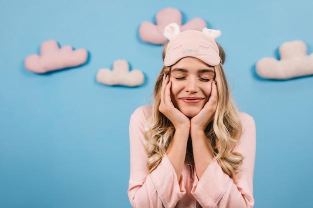 Mujer emocionada en antifaz para dormir sonriendo con los ojos cerrados