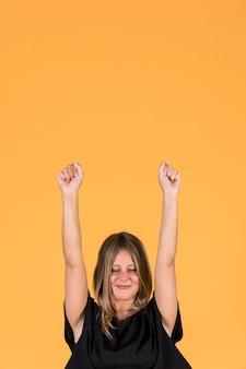 Mujer emocionada bombeando puños con los ojos cerrados sobre fondo amarillo