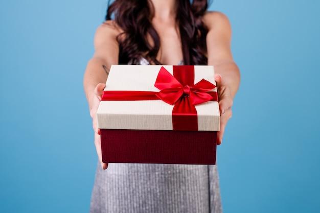 Mujer emocionada con caja de regalo con cinta roja con vestido aislado sobre azul