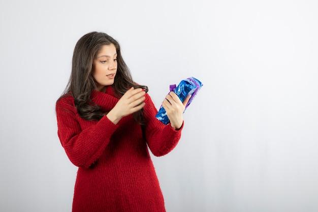 Mujer emocionada con una caja de regalo de navidad con cinta morada.