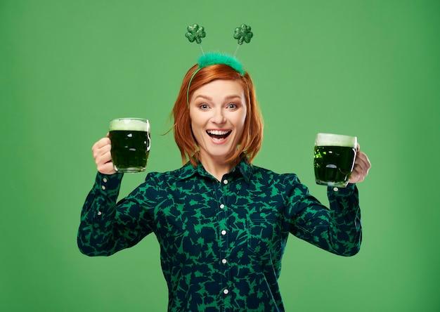 Mujer emocionada con cerveza haciendo un brindis