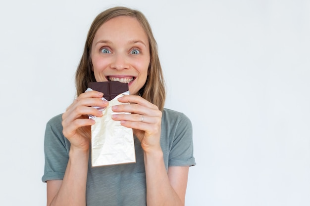 Mujer emocionada comiendo barra de chocolate en lámina de oro