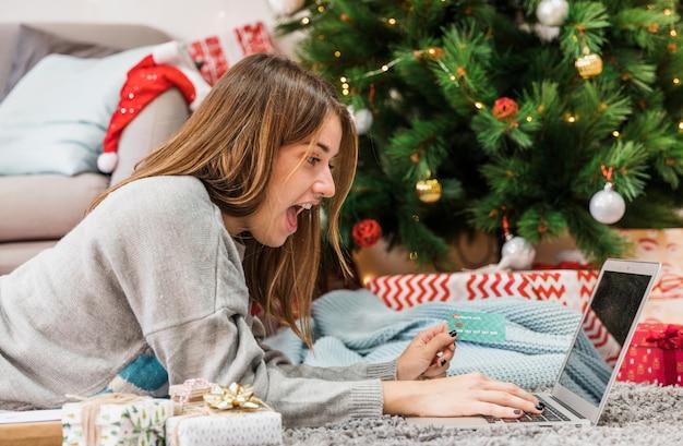 Mujer emocionada de compras en el árbol de navidad