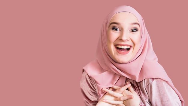 Mujer emocionada hermosa que mira la cámara contra superficie coloreada