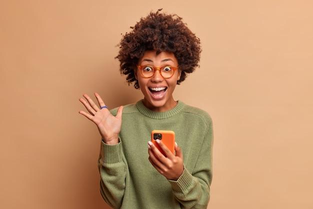 Mujer emocionada y llena de alegría con cabello afro levanta la palma tiene los ojos llenos de felicidad después de recibir excelentes noticias sostiene el teléfono móvil usa anteojos y lentes ópticos aislados sobre una pared marrón