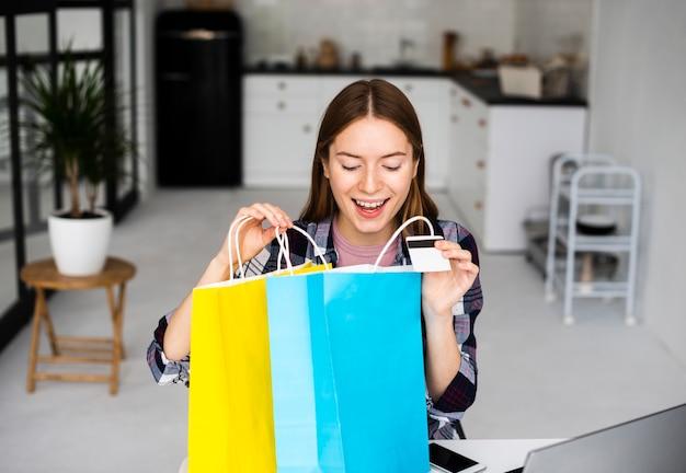 Mujer emocionada mirando dentro de bolsas de vacaciones
