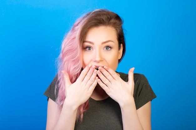Mujer emocionada con los ojos bien abiertos se cubre la boca con las manos