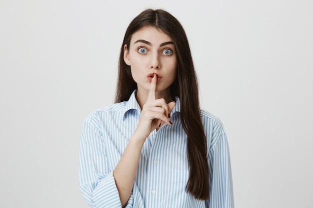Mujer emocionada pidiendo silencio, callando con el dedo índice presionado contra los labios
