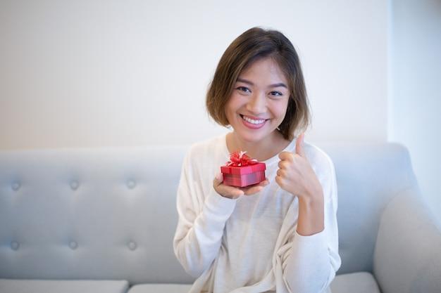 Mujer emocionada positiva con la pequeña caja de regalo que muestra el pulgar arriba