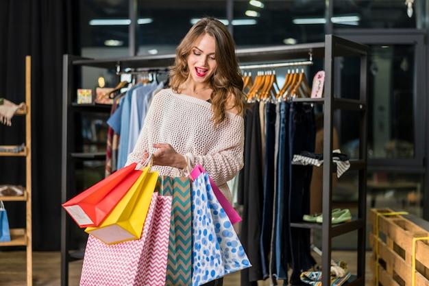 Mujer emocionada que mira bolsos de compras coloridos interiores