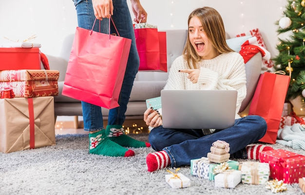 Mujer emocionada que señala en el bolso de compras