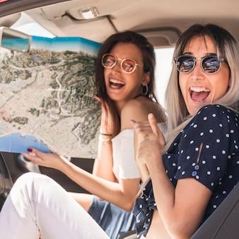 Mujer emocionada que se sienta al lado de su amigo que sostiene el mapa en el coche