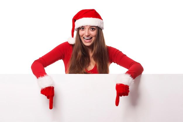 Mujer emocionada con sombrero de santa mostrando en cartelera en blanco