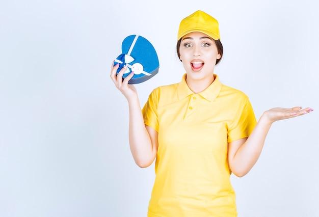 Mujer emocionada sosteniendo caja de regalo en una pared blanca