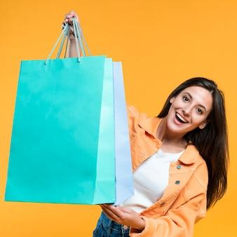 Mujer emocionada sosteniendo un montón de bolsas de la compra.