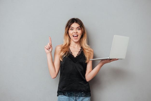 Mujer emocionada sosteniendo portátil y apuntando el dedo hacia arriba en copyspace