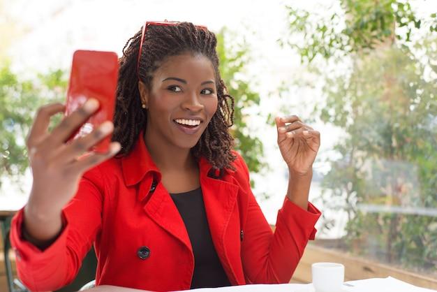 Mujer emocionada tomando selfie en café