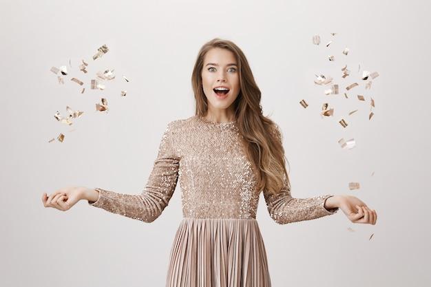 Mujer emocionada en vestido de noche lanzando confetty dorado