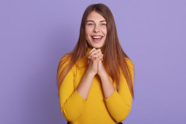 Mujer emocionada en vestimenta casual está riendo con las manos juntas
