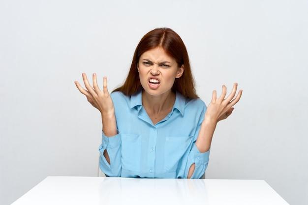 Mujer emocional en una camisa se sienta en el gesto de la mesa con las manos de la secretaria