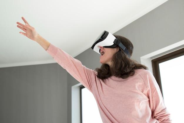 Mujer emocional emocionada apuntando hacia arriba mientras juega videojuego