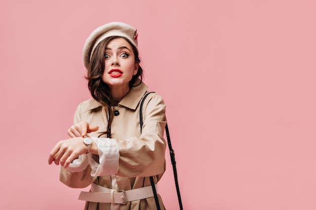 Mujer emocional en gabardina beige y sombrero de color claro mira a la cámara y señala el reloj de pulsera.